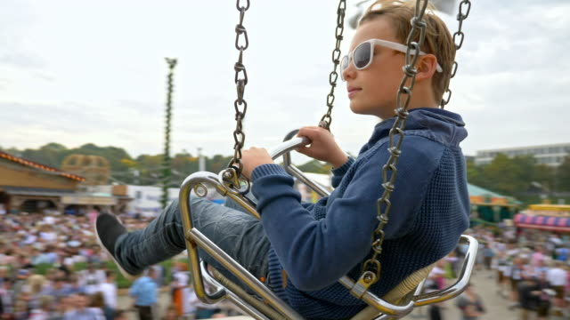 10 year old boy with white sunglasses takes a chain swing carousel ride while visiting the 'Oide Wiesn' during Oktoberfest 2017 - looking at camera