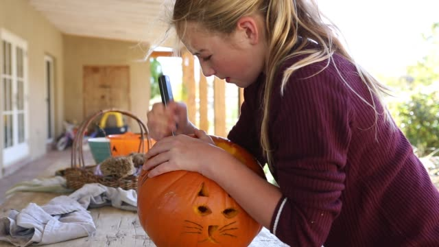 11 year old girl carving a pumpkin