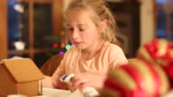 8 year old girl decorating a gingerbread house at Christmas