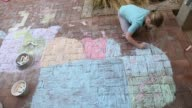 8 year old girl painting with chalk on brick patio