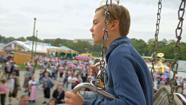 10 year old school boy takes a chain swing ride while visiting the 'Oide Wiesn' during Oktoberfest 2017 - thoughtful child