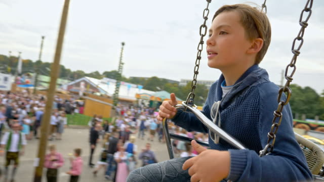 10 year old school boy takes a chain swing ride while visiting the 'Oide Wiesn' during Oktoberfest 2017 - blurred background