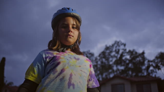 10 year old skater girl with skateboard on neighborhood street at dusk. Turn to camera. MED, tilt up and push in, jib