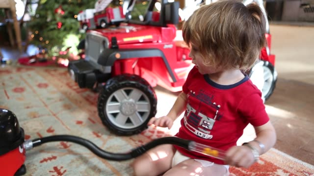 2 year old toddler boy playing with toy vacuum cleaner