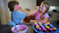 8 year old twins applying cupcake camouflage on their faces.