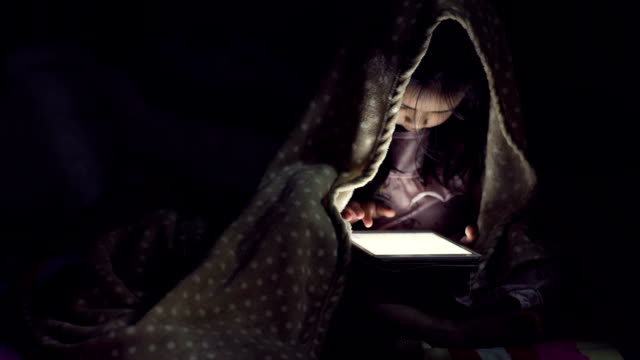 5 years old girl using a digital tablet in the dark