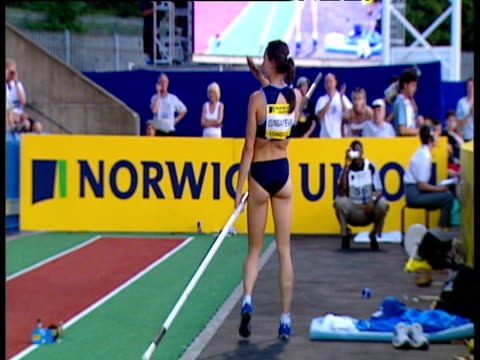 Yelena Isinbayeva is cheered and applauded by fans seconds after setting World Record puts baseball cap on lays pole on advertising hoardings and...