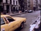 Yellow cab pulls up in run down street; 1970s