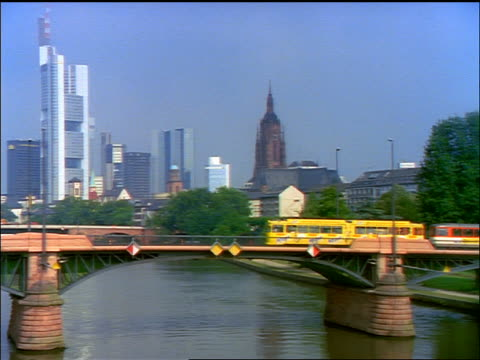 PAN yellow commuter train + traffic on bridge over Main River with Frankfurt skyline in background