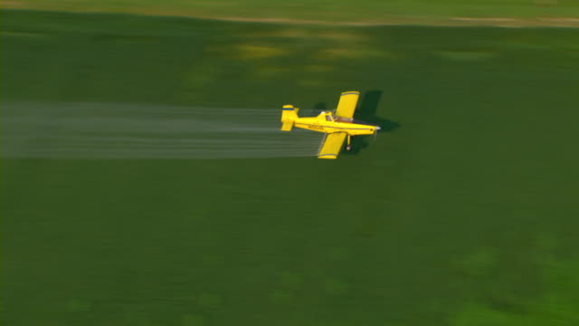 A yellow crop duster sprays crops with pesticide.