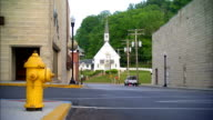 Yellow fire hydrant on street corner FG buildings amp Our Lady Of The Springs Catholic Church BG IN French Lick Indiana