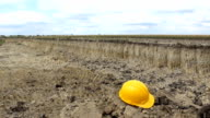Yellow helmet on thesoil ground left,it is a break time for lunch