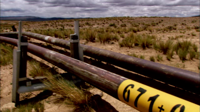 Yellow lettering and numbers identify a gas line in the Bolivian countryside. Available in HD.