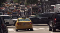 Yellow New York City taxi cab waits at traffic light as pedestrians use crosswalk ahead of it