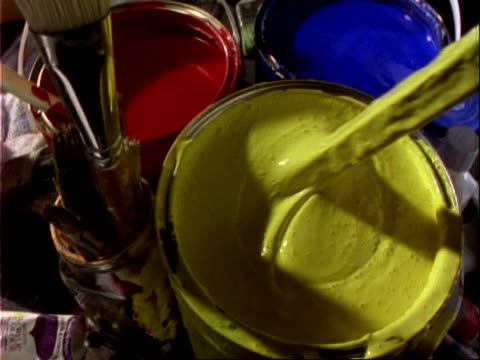 CU yellow paint being stirred, next to blue and red paint pots