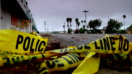 Yellow Police Line tape lying in pile near leaves moving slightly on pavement of parking lot near unidentifiable building street lights palm trees...