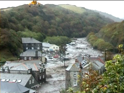 Yellow rescue helicopter hovers above badly flooded roads with cars left stranded by water Boscastle Cornwall 2004
