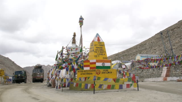 Yellow sign board and prayer flags at the Chang La Pass, Ladakh, India