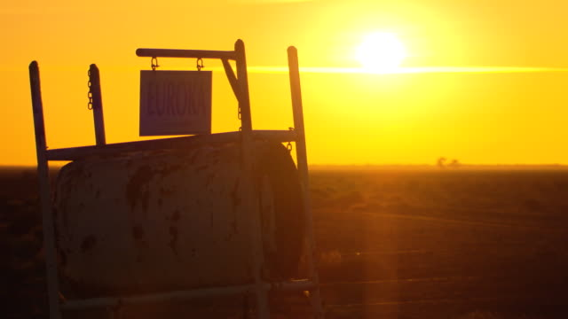 yellow sky and early morning sun over barren outback plain rustic 44 gallon 'mailbox' in close foreground for property 'Euroka' Change in exposure...