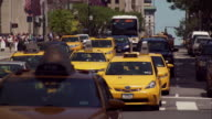 Yellow taxi cabs and buses move towards camera on busy New York City one way street
