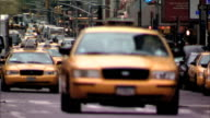 Yellow taxi cabs taxis cars trucks vehicles moving and stopping on congested street Flocks of unidentified pedestrians walking across street Traffic...