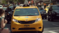 Yellow taxi van sits in traffic with hazards on in busy New York City intersection
