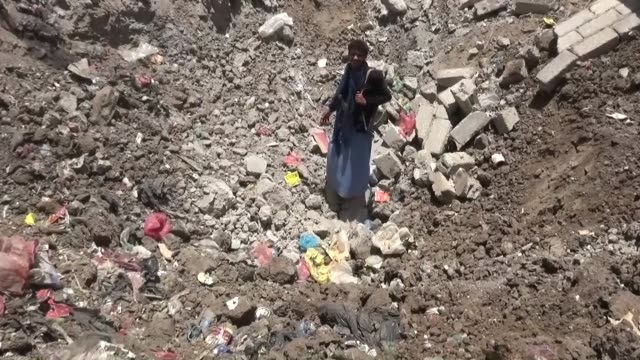Yemeni people inspect the debris of their houses heavily damaged after airstrikes staged by Saudiled coalition against Houthi bases to collect still...