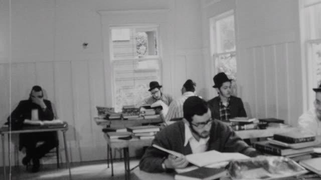 Yeshiva students pray in shul / Close ups of Talmudic study / Yeshiva at Chabad of Pacific Northwest on October 01 1975 in Seattle Washington