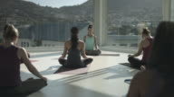 Yoga class doing stretching exercises, in rooftop studio