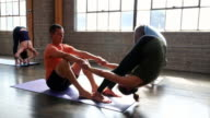 MS Yoga instructor assisting student in forward bend during class in studio