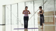 WS DS Yoga instructor assisting student in yoga studio / Vancouver, British Columbia, Canada