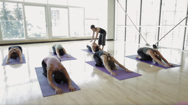 WS DS Yoga instructor instructing students in yoga studio / Vancouver, British Columbia, Canada
