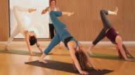 WS Yoga instructor leading class through various yoga poses / Austin, Texas, USA