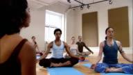 Yoga instructor leading students through meditation in yoga class