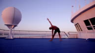 Yoga on ship in the evening - parsvakonasana and trikonasana