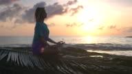 Yoga on the beach. Woman meditating in lotus pose. Sunset