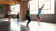 MS Yoga students practicing sun salutation sequence in beginning of class in studio
