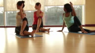 Yoga students practicing yoga in yoga studio