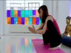Yoga teacher instructs class while in a 'Prayer Squat'