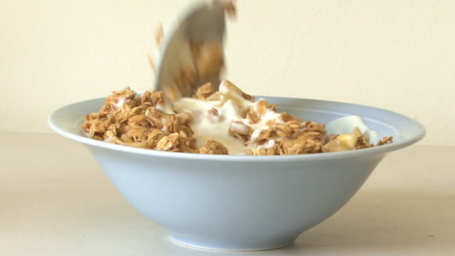 Yoghurt being spooned onto muesli in bowl
