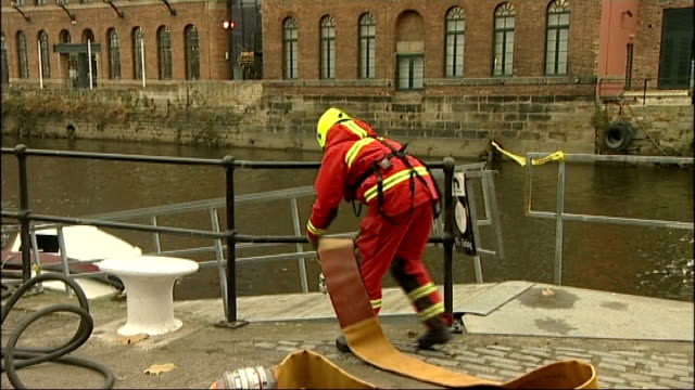 Leeds Members of West Yorkshire Fire and Rescue team testing high pressure pump next to river Aire Close shot of pump Firefighter feeding pump hose...