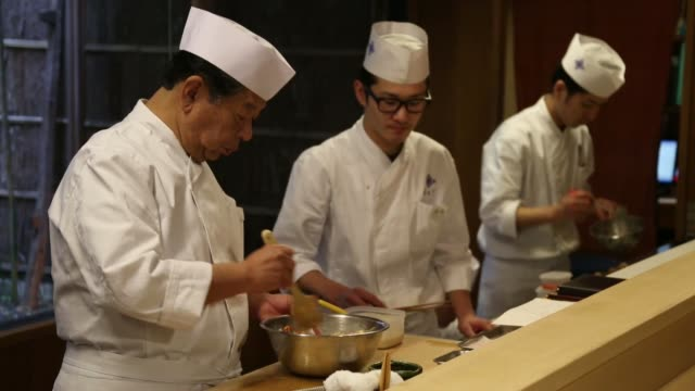 Yoshihiro Murata master chef for Kikunoi Japanese restaurant and chairman of the Japanese Culinary Academy cooks in the restaurant kitchen during a...