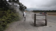 MS Yound lady in hiking clothes plays in geothermal steam rising out of ground alongside road at Volcanoes National Park / Volcano, Hawall, Big Island, United States