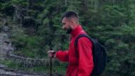 Aktive Jüngling mit Stöcken Wandern entlang Bergfluss