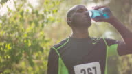 Young adult african american runner drinking water after race