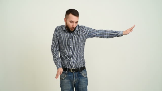 Young adult beard man having fun dancing on a gray background