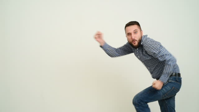 Junger Erwachsener Mann mit Bart, die Spaß tanzen auf einem grauen Hintergrund