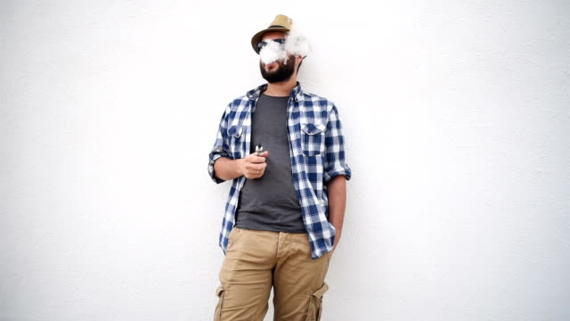young adult bearded man with an electronic cigarette standing near the wall