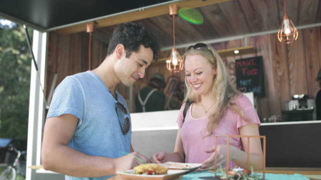 Young adult couple eating outside at food truck at music festival