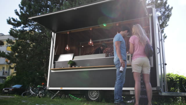 Young adult couple in queue for food at food truck